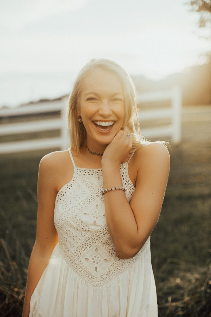 Lexi J. White dress senior pictures open field outdoor backlit smiling pose inspiration girl