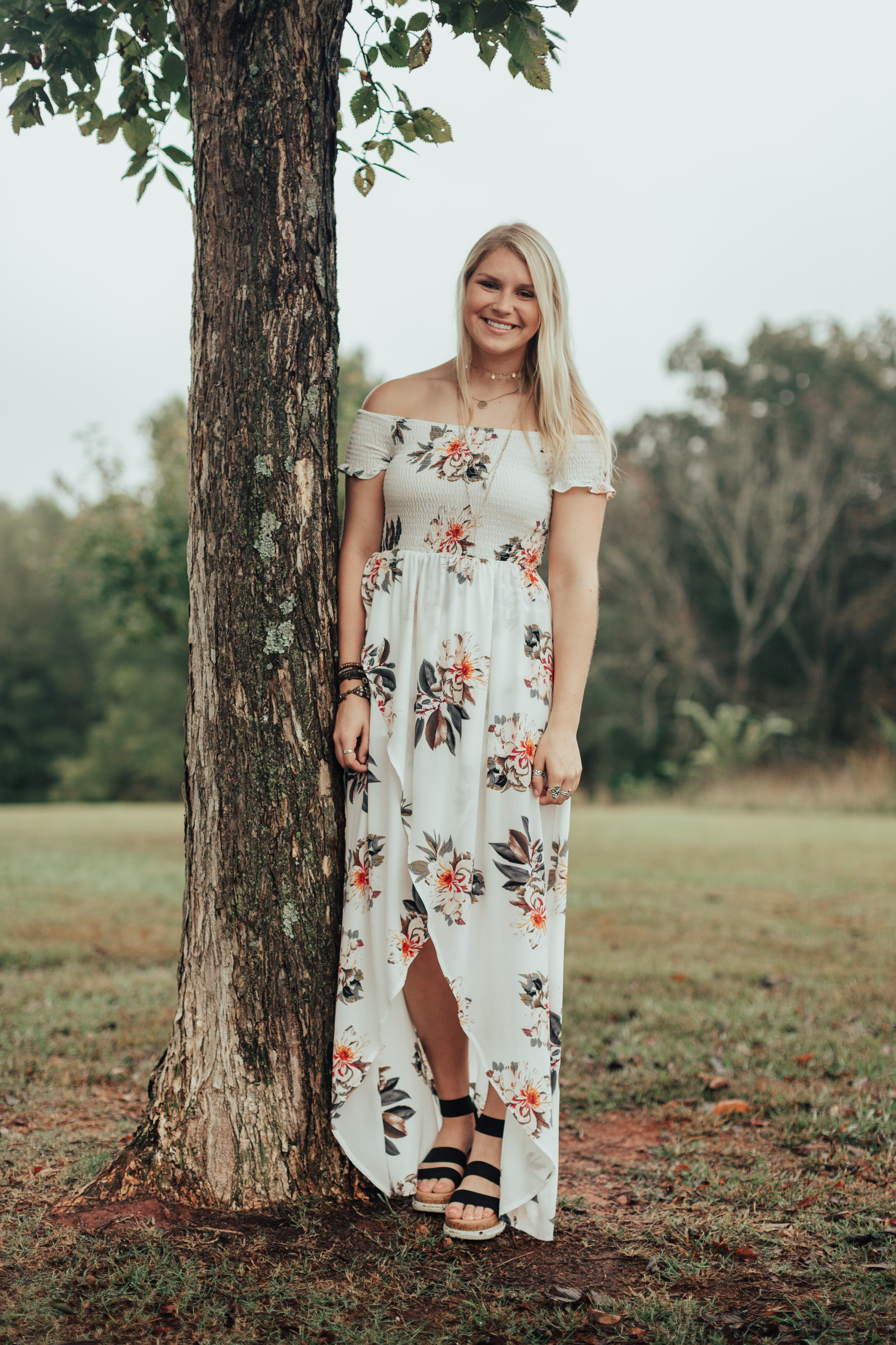 Jordyn S. senior pictures Wesleyan white floral dress idea poses white house outdoor field golden hour bride dress wedding dress gold necklaces Olie West