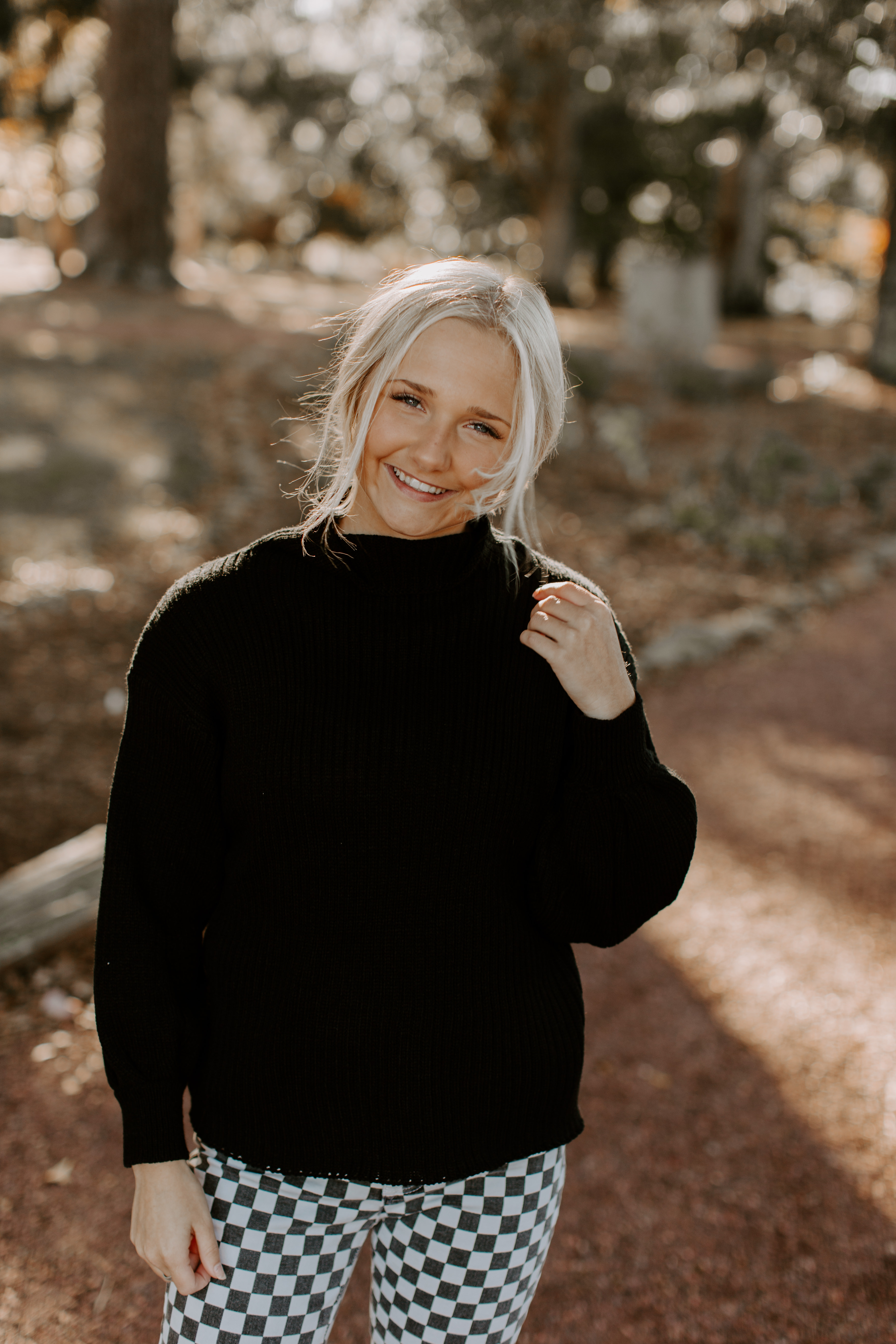 Ashley W. free people senior pictures black sweater checkered pants lifestyle city candid model pose wedding elopement blonde hair outfit overall white preset