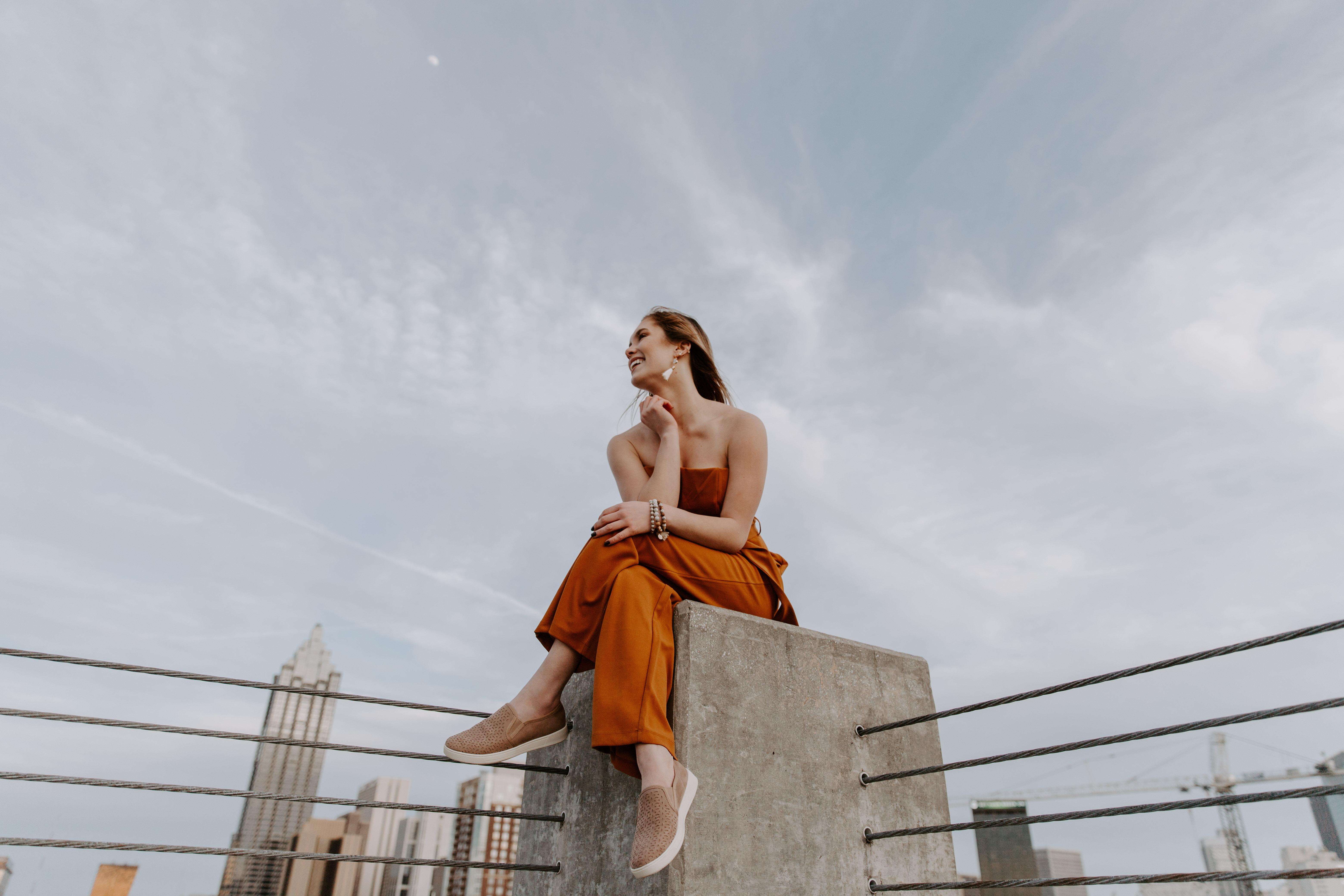 Zoe White Senior Pictures Atlanta Orange Dress Jean Jacket Portrait Pose Laughing Alpharetta